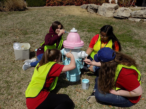 Staff photo by Mike Elswick<br /> Youth Volunteer Corps of Muskogee volunteers spent the afternoon of the first day of spring Tuesday priming and painting city fire hydrants along Denison Street. From left foreground clockwise, are Allee Phillips, Whitley Glass, Valencia Rodriquez and Ashlyn Goad. This hydrant was to sport a cupcake look when completed, while others along the street will have gardening and animal themes, said Eileen Vankirk, YVC director for Muskogee Parks and Recreation Department.