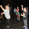 "CATHY SPAULDING/Muskogee Phoenix<br /> Dance instructor Francie Martin, left, shows Allie Goss how to play an invisible bass guitar during dance rehearsals for ""Beat Bugs."" Muskogee Little Theatre will present the Spring Break Camp production Friday, Saturday and Sunday."