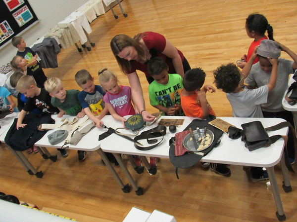 Staff photo by Cathy Spaulding<br /> Sadler Arts Academy kindergartners examine Civil War artifacts under the guidance of librarian Mandy Cumbey. The artifacts are part of the Oklahoma History Center's Traveling Trunk program.