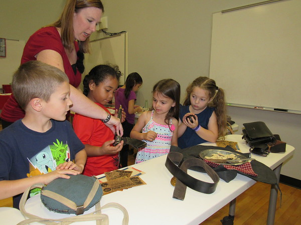 Staff photo by Cathy Spaulding<br /> Sadler Arts Academy Librarian Mandy Cumbey shows the safe handling of an artifact to kindergartners, from left, Wyatt Hill, Aries Arlen, Lexi Speir and Embri Watson. The artifacts are part of a Traveling Trunk exhibit from the American History Center.