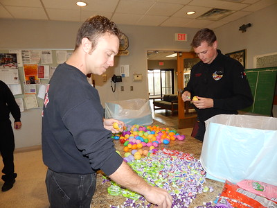 Staff photo by Kenton Brooks Anthony Hollifield, left, and Eric Butler fill Easter eggs with candy at Fire Station 1 on Columbus Avenue to prepare for the Easter Egg Hunt at Spaulding Park on Saturday.