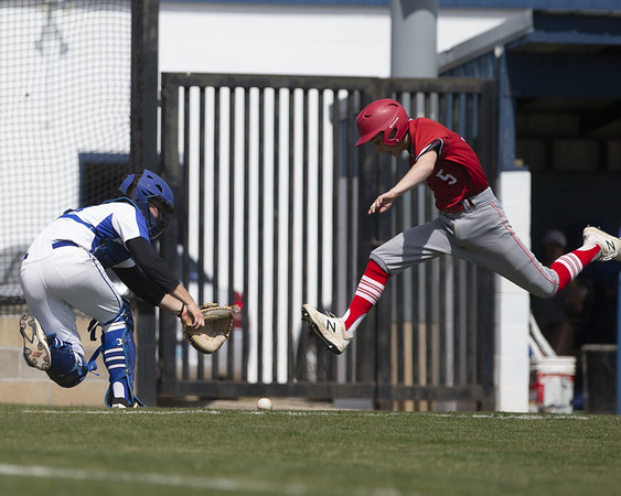 VON CASTOR/Phoenix Special Photo<br /> Fort Gibson's Grant Edwards jumps over the incoming throw to score the winning run Friday afternoon at Checotah. The Wildcats' Collin Roberts tries to make the play.