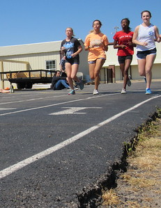 Staff photo by Cathy Spaulding Warner High School runners, from left, Madison Ramming, Bailey Epps, Jaelisa Tolbert and Callie Glisson run on the school's asphalt track. School officials hope to resurface the track if a $340,000 bond issue passes.