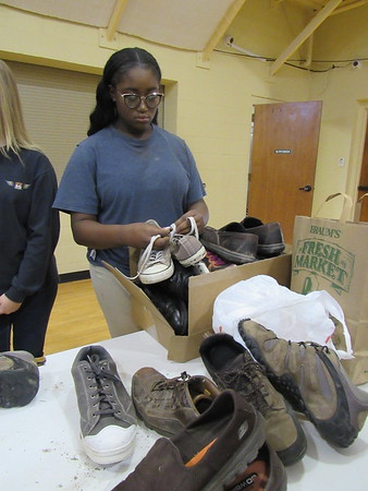 CATHY SPAULDING/Muskogee Phoenix Asharia Jones of St. Paul United Methodist Church puts donated shoes in a box. Church youth will take shoes on a mission trip this summer.