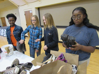 CATHY SPAULDING/Muskogee Phoenix St. Paul United Methodist Church youth, from left, Aspen Jones, Melysa Cobb, Kelie Cobb, Asharia Jones sort shoes they'll take on a mission trip to Nashville. The group Soles4Souls distributes the shoes to developing countries.