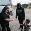 CATHY SPAULDING/Muskogee Phoenix<br /> Muskogee Public Schools Child Nutrition Services worker Betty Hammond gives chocolate milk to Benjamin Boyd, 2, while Muskogee High School student Alexis Boyd watches. Hammond distributed school lunches Monday at Green Country Village.
