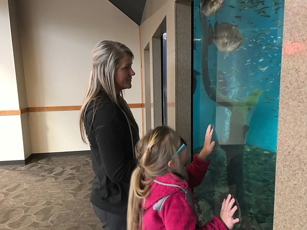 Special photo by Travis Sloat Payton Crum, 7, along with her mother Paige Mannon watch the fish swim in the tank at Arrowhead Mall. Payton was born with Optical Nerve Hypoplasia, and her family is seeking help to purchase eSight glasses which would give her 20/20 vision.