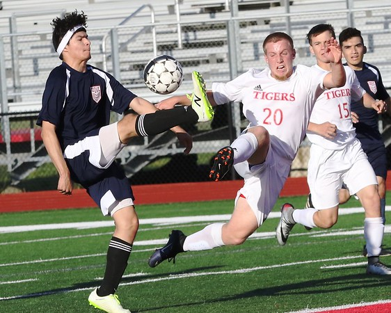 Phoenix special photo by John Hasler<br /> Fort Gibson's Jace Walker, right, battles Dove Science's Nestor Chavez for the ball in Friday's soccer clash at Fort Gibson. In the background is the Tigers' Trapper Taylor.