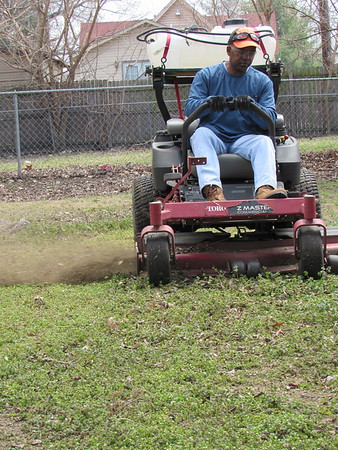 Staff photo by Cathy Spaulding<br /> Darryl S. Brown mows a lawn near downtown Muskogee. He began doing lawn work as a side job and now has his own business.