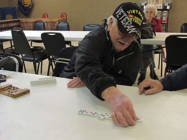 CATHY SPAULDING/Muskogee Phoenix<br /> Larry Settlemyre plays a domino at the Fort Gibson Senior Nutrition Center, which meets at the Frank Gladd American Legion Post 20.