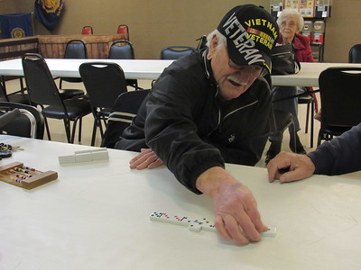 CATHY SPAULDING/Muskogee Phoenix Larry Settlemyre plays a domino at the Fort Gibson Senior Nutrition Center, which meets at the Frank Gladd American Legion Post 20.