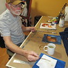 SPAULDING/Muskogee Phoenix<br /> James Harelson dries a paintbrush after adding a finishing touch to the still life he painted on Wednesday, the first day of a Five-Day Painting Challenge.