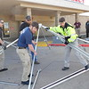 KENTON BROOKS/Muskogee Phoenix<br /> Muskogee County EMS Region 4 Disaster Medical Response team members Jay Brown, left, and Colby Menie put down poles for the mobile triage tent at the Saint Francis Hospital Muskogee Emergency Room entrance Wednesday. Christopher Turner and Chris Tinsley bring more poles to assist in the operation. The Oklahoma Department of Health sent tents to be used for the triage to Muskogee County EMS and the triage will be operated by the hospital.