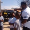 Staff photo by Mike Kays<br /> Muskogee native Robert Thomas talks to kids at a block party in his honor Saturday on North Junction outside G Styles barbershop.