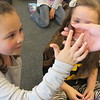 CATHY SPAULDING/Muskogee Phoenix<br /> McKenzie McCormick, 6, touches the back of a hissing cockroach during a spring break visit to Q.B. Boydstun Library. An educator from the Oklahoma City Zoo brought a cockroach, chinchilla, armadillo and a tarantula to the library on Wednesday.