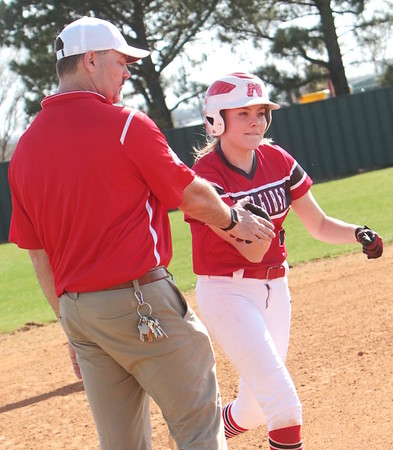 JOHN HASLER/Special to the Phoenix<br /> Maddi Jo Williams gets congratuations from Fort Gibson coach Scott Lowe after a solo home run in game one, one of two she had in a 10-0 win over Checotah. The Lady Tigers won game two, 10-1.