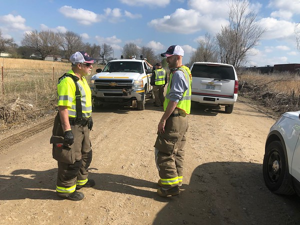 CHESLEY OXENDINE/Muskogee Phoenix<br /> Oktaha Fire Chief John Stout converses with fireman Zach Sanders at the scene of a pedestrian-train collision Tuesday morning.