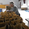 KENTON BROOKS/Muskogee Phoenix<br /> Capt. Dodie Swartz of Wagoner prepares bags for food at The Salvation Army on Thursday. The food will be delivered or handed out to those in need. Swartz, a volunteer, said she wanted to give back to the community and offered her help along with her husband Ric in getting the bags ready.