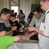 Staff photo by Cathy Spaulding<br /> Youngsters including, from second from left, Ryan Alley and Noah Kitchens, help Fort Gibson Historic Site worker Rory Montgomery, second from right and volunteer Brendan Crotty make bread loaves during the site's Bake Day.