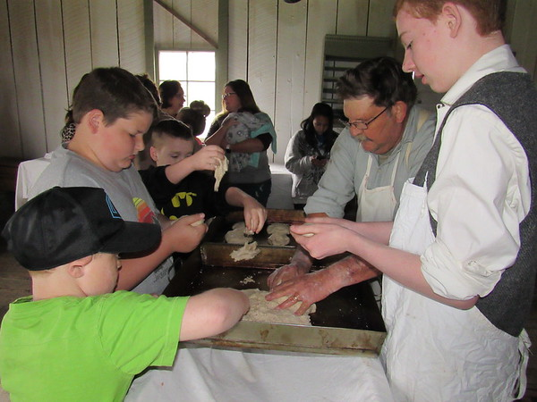 Staff photo by Cathy Spaulding Youngsters including, from second from left, Ryan Alley and Noah Kitchens, help Fort Gibson Historic Site worker Rory Montgomery, second from right and volunteer Brendan Crotty make bread loaves during the site's Bake Day.