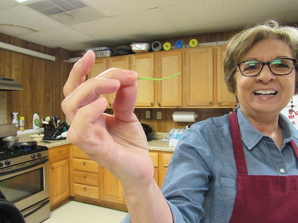 CATHY SPAULDING/Muskogee Phoenix<br /> Thin, flat wild onion leaves, like this one held by Vinnie Hoover, add color to the wild onion and scrambled egg dishes. Fife Indian United Methodist Church will sponsor a Wild Onion Dinner on Friday.