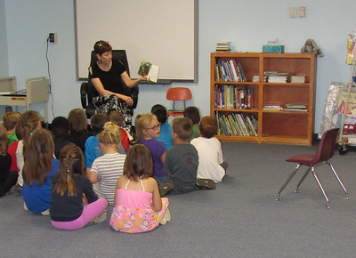 Staff photo by Cathy Spaulding Ellington Early Childhood Center Librarian Cheryl Blair reads to students in the school library. The school received a $15,000 grant from Dollar General Literacy Foundation to replace books and other items damaged in a July storm.