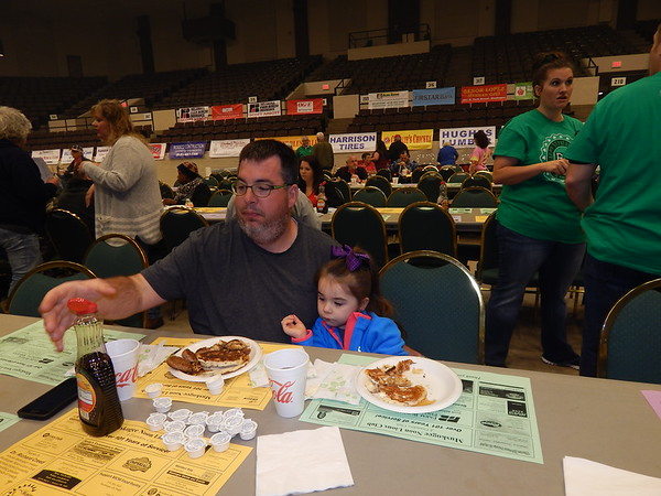 KENTON BROOKS/Muskogee Phoenix<br /> Andrew Nail of Muskogee reaches for the syrup as he and 4-year-old daughter Chalie eat pancakes at Wednesday's Muskogee Noon Lions Club Pancake Breakfast at the Muskogee Civic Center.