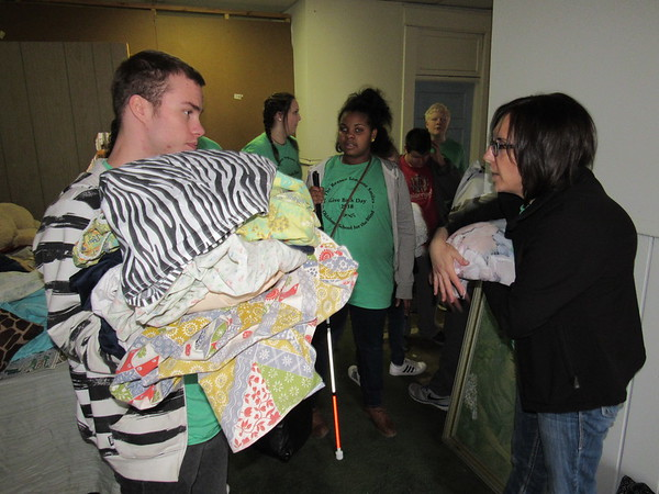 CATHY SPAULDING/Muskogee Phoenix<br /> Oklahoma School for the Blind student Cameron Hughes holds a stack of bed linens he just folded, while OSB Family and Consumer Science Teacher Allison Garner gives instructions during OSB Give Back Day. Students spent Wednesday morning sorting linens at Gospel Rescue Mission.
