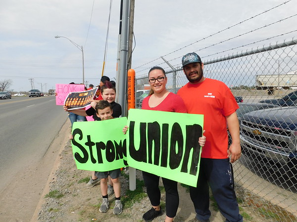 KENTON BROOKS/Muskogee Phoenix<br /> Jon Hammons, right, stands outside Owens-Illinois on Thursday with his family and fellow workers to bring attention to the United Steelworkers contract negotiations with the company during a national day of solidarity. Also pictured, from right, are his wife, Alicia, and sons Jadon and Levi.