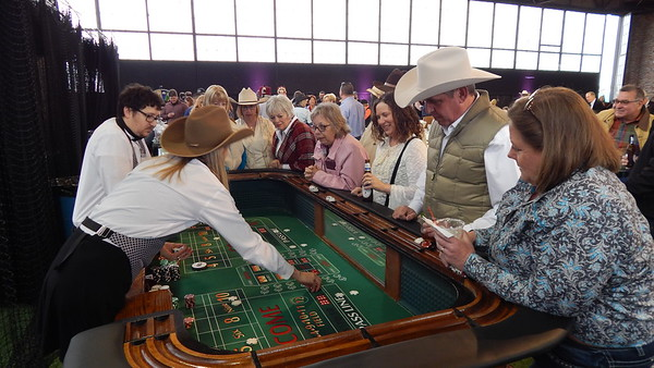 Staff photo by Wendy Burton<br /> Cowboys and cowgirls shoot craps, betting with play money, at the 94th annual Greater Muskogee Area Chamber of Commerce Banquet on Thursday. The annual banquet was held in the Hangar this year.
