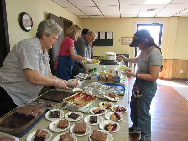 Church volunteer Betty Berthold, left, serves a cobbler while Cushing agriculture student Lara Allen puts dressing on her salad Wednesday during the Baptist Collegiate Ministry noonday lunch across from Connors State College's Warner campus.