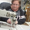 CATHY SPAULDING/Muskogee Phoenix<br /> LaDonna Scott of Thayer Upholstery attaches straps to precut and prefolded fabric while making medical face masks on Saturday.