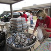 CATHY SPAULDING/Muskogee Phoenix<br /> Cashier Connie Melton bags milk and drinks while helping Fort Gibson Schools child nutrition workers carry food to drivers.