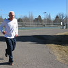 Staff photo by Cathy Spaulding<br /> Jim Webb does a lap around the tennis courts parking lot at Honor Heights Park during a mid-morning run. He has run marathons in Boston and Dallas.