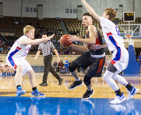 Phoenix special photos by Samuel Perry<br /> Okay's Caleb Riggs, center, splits the defense for two of his game-high 27 points during Saturday's Class A boys championship game at State Fair Arena in Oklahoma City. Okay lost 67-52.