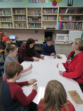 CATHY SPAULDING/Muskogee Phoenix<br /> Fifth-graders — clockwise from bottom, Cameron Rice, Clayton Abel, Teagan Graves, Jessica Veracruz and James Reed — surround teacher Angela Marshall in a small group session. They are able to write on top of the new dry-erase table.