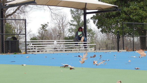 Staff photo by Cathy Spaulding<br /> Wind whips leaves across the Spaulding Park tennis court while Jocelyn Robinson takes a break in the court bleachers Monday afternoon.