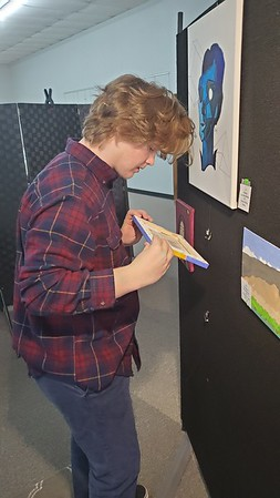 CHESLEY OXENDINE/Muskogee Phoenix<br /> Porum High School sophomore Preston McBay hangs a painting during preparation for the Muskogee Art Guild's student art show, running through March 30.