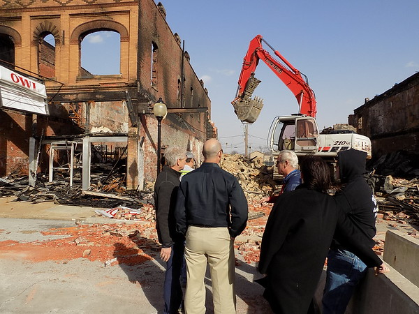 Staff photo by Mike Elswick Wagoner Mayor Albert Jones, left, discusses with others demolition of a historic downtown building Tuesday afternoon after high winds caused the burned-out facade to sway, resulting in public safety concerns.