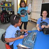 CATHY SPAULDING/Muskogee Phoenix<br /> Braille Challenge proctor Bundy Porterfield ofNewView, standing, gives headphones to Oklahoma School for the Blind senior Ariana Richardson,left, while OSB senior Richelle Zampella sets up for competition.