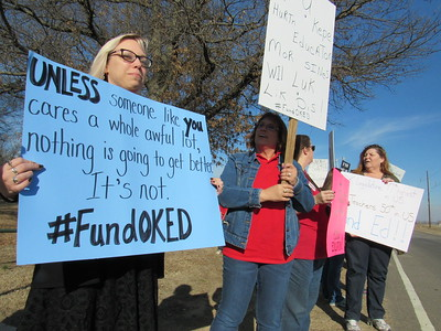 Staff photo by Cathy Spaulding Cherokee Elementary librarian Gina Batie, left and Creek Elementary teacher Angela Cummings share their sentiments during a Thursday afternoon protest at Muskogee High School.