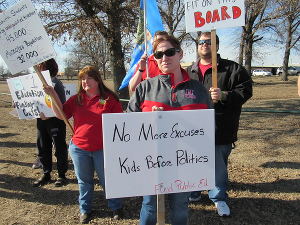 Staff photo by Cathy Spaulding<br /> Hilldale Public Schools paraprofessional Milissa Watson, center, joins a Thursday afternoon protest outside Muskogee High School.
