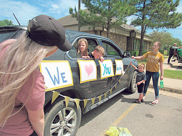 Kim Perry and her children — from second left, Adalyn, 9, Zabryn, 7, Ecklyn, 4 and Sophia, 12 — decorate her vehicle before joining Friday's parade in front of Fort Gibson Nursing Home, where Perry's mother is a resident.