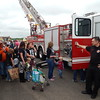 Staff photo by Mark Hughes<br /> Firefighter Jefferson Bowman holds open a firetruck's door so children can crawl in to see what it's like inside during the Touch-a-Truck benefit Saturday at Davis Field. Station 1 provided the firetruck. A firetruck, dump truck, garbage truck, milk truck, an ambulance, and even model airplanes were among the vehicles on display.