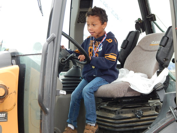 Staff photo by Mark Hughes<br /> Kash Brunson, 5, imagines the delight of driving a backhoe at Touch-A-Truck.
