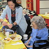 CATHY SPAULDING/Muskogee Phoenix<br /> Jessica Vickrey of OG&E, left, helps Thelma Kitchen sweeten her coffee during the recent Golden Agers Breakfast. The breakfast has been a Fort Gibson tradition for more than 35 years.
