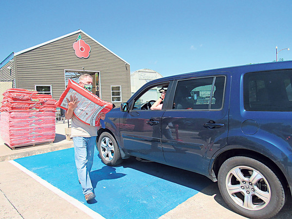 Blossom's Garden Center co-owner Matthew Weatherbee carries potting mix to a customer's vehicle. The center is doing business online and curbside only this season.