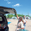 CATHY SPAULDING/Muskogee Phoenix<br /> Blossom's Garden Center co-owner Lora Durkee uses gloves and a rag to close a customer's tailgate after loading an order. Co-owner Matthew Weatherbee watches.