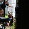 Staff photo by Harrison Grimwood<br /> Muskogee police officers enter an unoccupied home through a base- ment window Monday in the 1300 block of Emporia Street to search for a suspect in an armed robbery earlier in the day.
