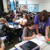 "Staff photo by Wendy Burton<br /> Whittier Elementary teacher Nelita Cash helps students in her classroom, wearing purple for ""Purple Tuesday"" to increase Alzheimer's awareness. Whittier was designated a National School of Character, in part for its fundraising efforts for Alzheimer's research and also for its many character-building programs and activities."